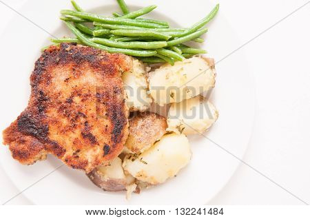 pan searched pork chop breaded with herbs and spices with herb encrusted potato and haricote vert
