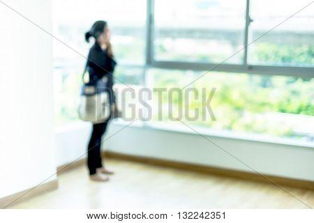 Blurred background : woman talk on phone at condominium room.