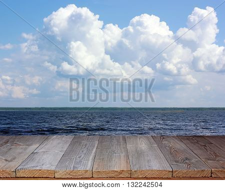 Empty wooden deck on the background of sea and sky with clouds. Empty space for.