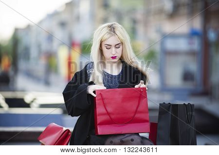 Beautiful young stylish blonde woman in black coat with shopping bags sitting on a bench in the park