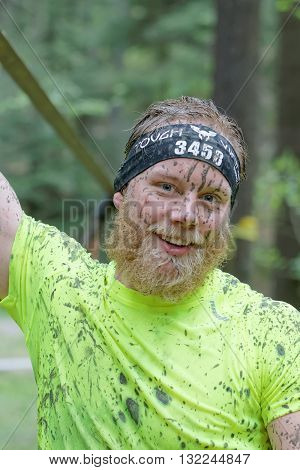 STOCKHOLM SWEDEN - MAY 14 2016: Smiling man with beard and mud in his face in the obstacle race Tough Viking Event in Sweden April 14 2016