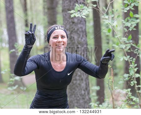 STOCKHOLM SWEDEN - MAY 14 2016: Smiling woman making victory sign in the obstacle race Tough Viking Event in Sweden April 14 2016