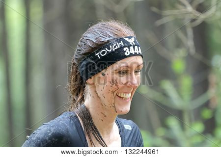 STOCKHOLM SWEDEN - MAY 14 2016: Smiling woman with mud in her face in the obstacle race Tough Viking Event in Sweden April 14 2016