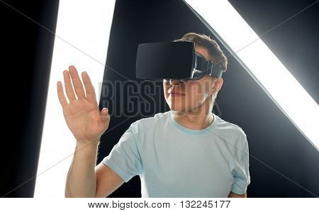 3d technology, virtual reality, entertainment, cyberspace and people concept - happy young man with virtual reality headset or 3d glasses playing game and touching something
