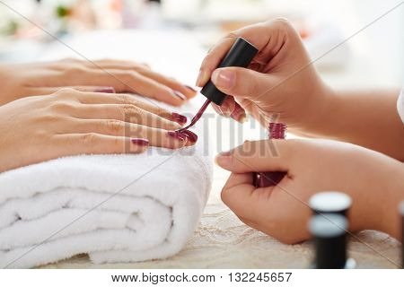Side view of manicurist applying marsala nail polish