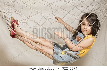 Small girl suspended inside net isolated in background