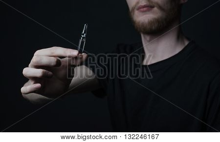 Addiction Topic: Addict Holds A Vial Of A Drug On A Dark Background
