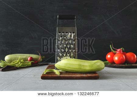 Marrow with grate on a wooden cutting board closeup on a light table on a dark background with space for your text. Cooking useful food