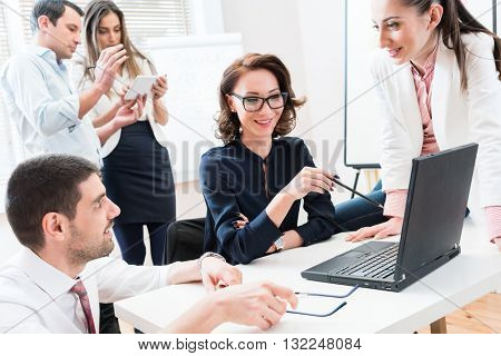 Team giving business report to boss in office meeting