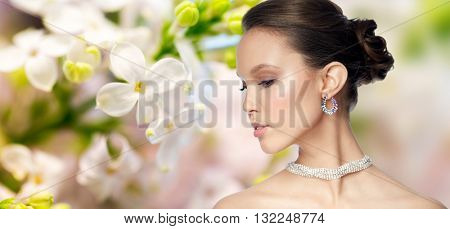 beauty, jewelry, accessories, people and luxury concept - close up of beautiful asian woman face with earring over natural spring lilac blossom background