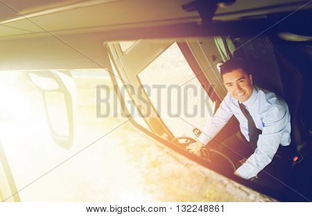 transport, transportation, tourism, road trip and people concept - close up of smiling driver reflection in passenger bus mirror