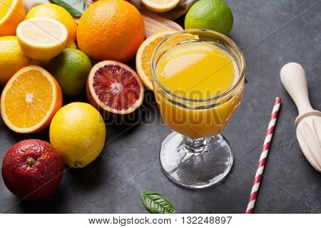 Fresh ripe citruses and juice. Lemons, limes and oranges on dark stone background
