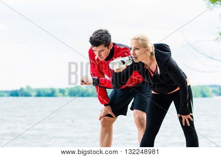 Woman and man at break from running in front of lake