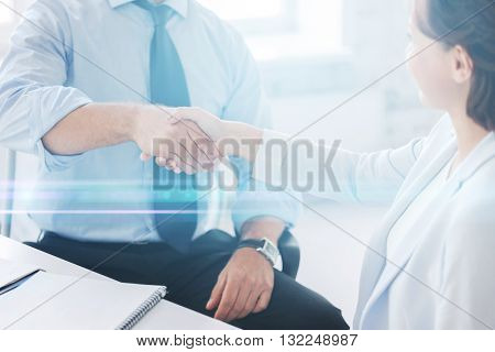 businesss and office concept - businessman and businesswoman shaking hands in office