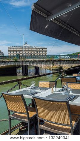 Bayonne France - May 21 2016: Bistro terrace next to Pont Mayou bridge over Le Nive river with Hotel de ville (City Hall) of Bayonne called Mairie de Bayonne in background. Aquitaine France