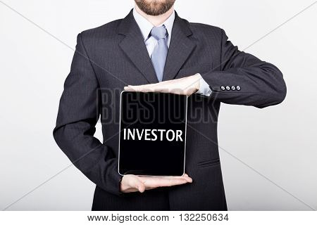 technology, internet and networking in business concept - businessman holding a tablet pc with investor sign. Internet technologies in business.