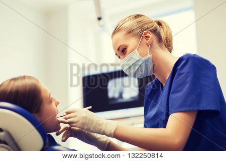 people, medicine, stomatology and health care concept - happy female dentist with mirror or dental probe checking patient girl teeth up at dental clinic office