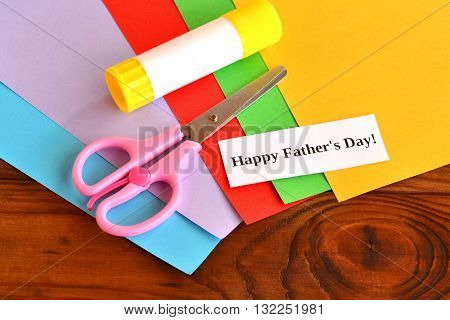Sheets of colored paper, glue stick, scissors, a piece of white paper with the words Happy father's day. Idea for easy to make father's day gift. Easy fathers day crafts. Art project for kids.