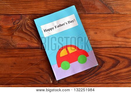 Greeting card with text Happy father's day and car applique. Greeting card on a wooden table. Father's day gift for kids to make. Original handmade gift. Home children paper diy