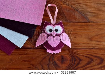 Burgundy and pink felt owl toy. Owl ornament. Stuffed owl sewing pattern.Felt bird plush softie. Keychain rearview mirror. Decoration mobile attachment. Home decor idea. Felt pieces. Wooden background