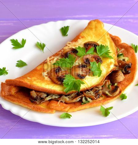Omelet with fried mushrooms, cheese and fresh parsley. Yummy veggie omelet on a plate and purple wooden background. Egg omelette vegetarian recipe. Homemade organic vegetarian food for breakfast.