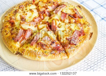 Medium Pizza and ham scorched on wood plate.