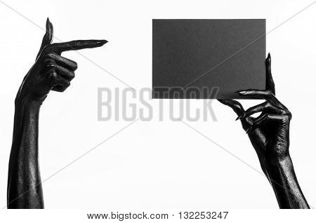 Halloween And Gothic Theme: The Black Hand Of Death Holding A Blank Black Card On White Isolated Bac