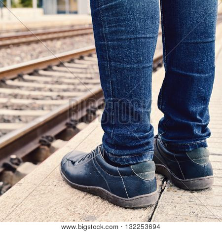 closeup of the feet of a young man wearing jeans who is waiting for the train at the platform of the train station