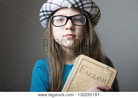 serious girl in glasses and checkered hat with English book in hands