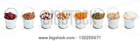 Assortment of beans, lentils, chickpeas, buckwheat, rice and oatmeal in decorative galvanized buckets isolated on white background