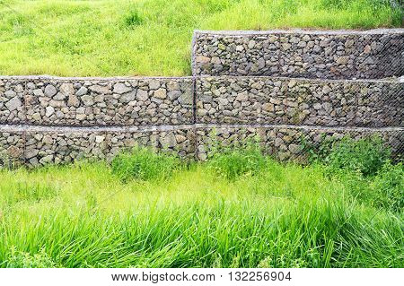 Wire mesh reinforcement with rock and green grass
