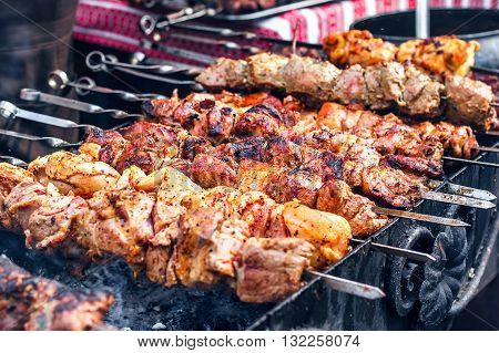 Marinated shashlik preparing on a barbecue grill over charcoal. Shashlik or Shish kebab popular in Eastern Europe. Shashlyk (skewered meat) was originally made of lamb. Roast Beef Kebabs On BBQ Grill.