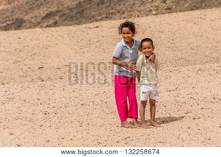 Sharm El Sheikh Egypt - May 07 2014: Barefoot children in tattered clothes in a Bedouin village posing for photos.