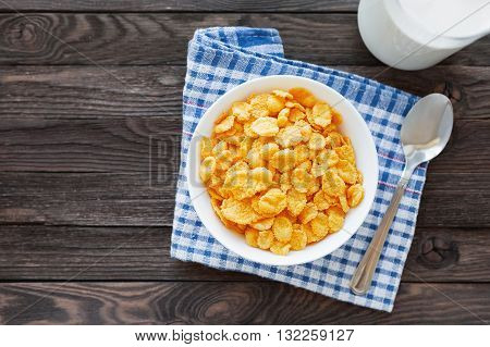 Tasty corn flakes in bowl with bottle of milk. Rustic wooden background with plaid tartan napkin. Healthy crispy breakfast snack. Place for text. Top view flat lay.