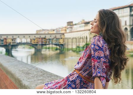 Relaxed Woman In Dress Sitting On Embankment Near Ponte Vecchio