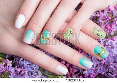 Beautiful turquoise manicure with crystals on female hand. Close-up. Picture taken in the studio