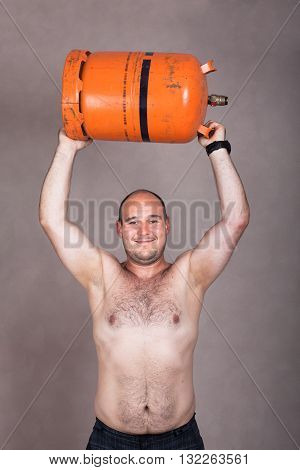Portrait of happy strong shirtless worker man lifting heavy gas bottle.