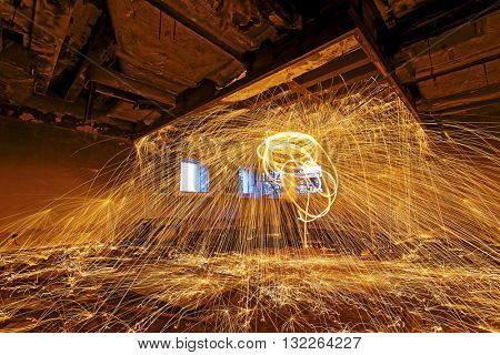 Burning Steel Wool spinning. Showers of glowing sparks from spinning steel wool in ruins