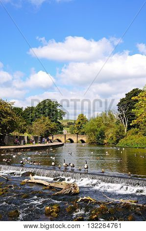 BAKEWELL, UK - SEPTEMBER 7, 2014 - View along the River Wye towards the medieval bridge with a weir in the foreground Bakewell Derbyshire England UK Western Europe, September 7, 2014.