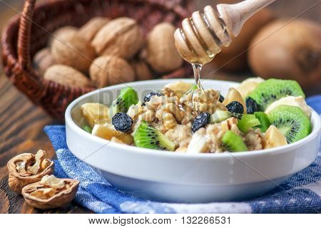 Organic oatmeal porridge in white ceramic bowl with bananas, honey, walnuts, kiwi fruit and raisins. Healthy breakfast - health and diet concept on the wooden table, close up.