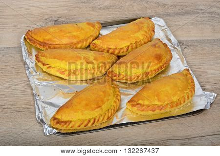 Six freshly cooked homemade vegetarian pasties on an oven tray against a wooden background.
