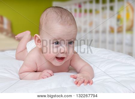 Adorable Crawling Baby Girl Lying On Belly.