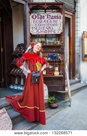 Tallinn Estonia - May 29 2016: Beautiful girl in red national medieval dress near medieval shop Olde Hansa in the Historical Centre of Tallinn city. Tallinn Estonia.