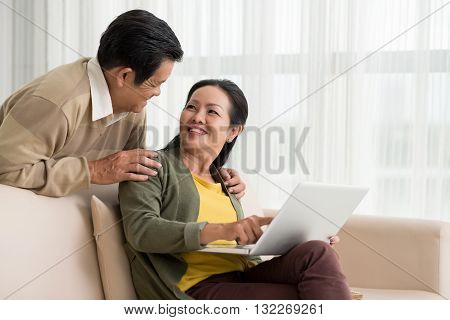 Smiling mature woman discussing something on laptop with her husband