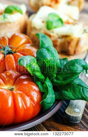 Fresh tomatoes with basil for use as cooking ingredients with copy space. Tomatoes with basil on wooden table background. Food composition.