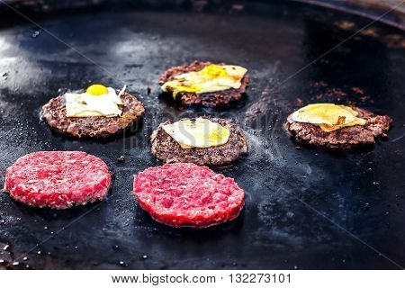 Cooking beef and pork patty with eggs and cheese for burger. Meat roasted on fire barbecue kebabs on the grill. Grilled burger cutlet beef minced meat patties or frikadeller in a pan. Street food.