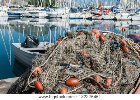 Detail of a fishing net in the harbor of Palermo with boats in background