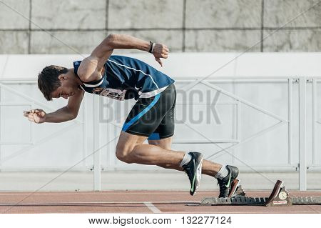 Chelyabinsk Russia - May 24 2016: male runner starts from starting blocks on a distance of 400 meters during UrFO Championship in athletics