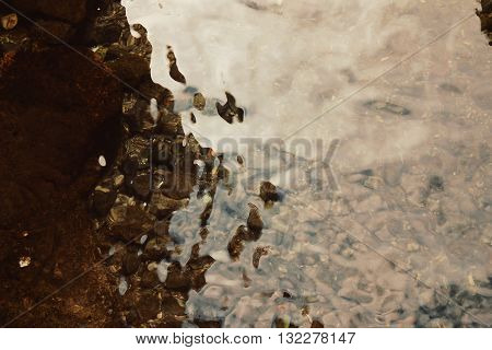 Shallow water with pebbles in the bottom. Aged photo with copy space area. River bottom with pebbles. Ripples on the surface of the lake. Vintage filter photo. Pebbles through the water.