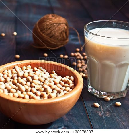 Glass of soy milk and full bowl of soy beans on wooden background. Ingredients for vegan or vegetarian cuisine